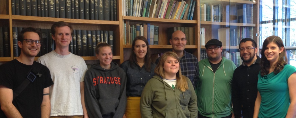 Syracuse University Geography Graduate Students standing in the James Library, looking happy.